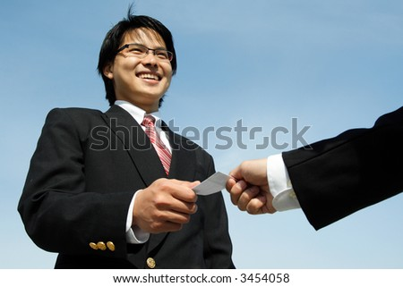 A businessman receiving a business card from his business partner - stock photo