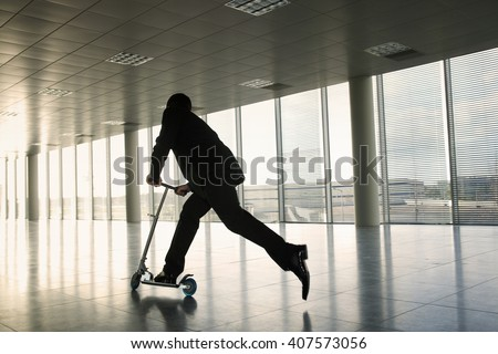 A businessman riding a scooter in an empty office - stock photo