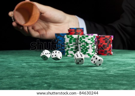 A businessman rolling the dice in a gambling game.