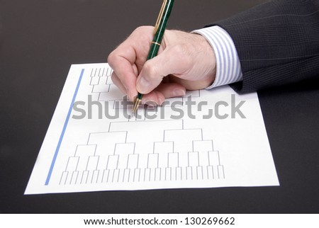 A businessman's hand holding pen completing March Madness bracket - stock photo