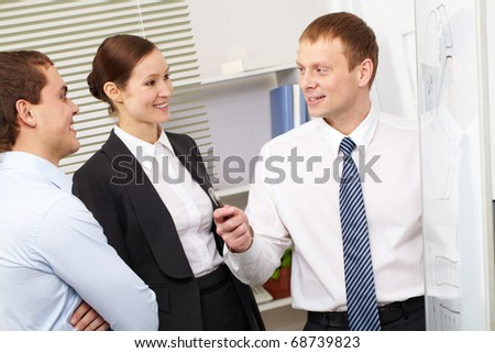 A businessman showing a plan to his colleagues - stock photo