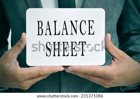 a businessman showing a signboard with the text balance sheet written in it - stock photo
