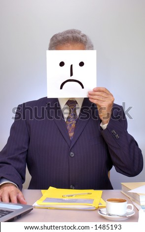 A businessman sits at his desk, holding a home-made sad-faced mask in front of him. - stock photo