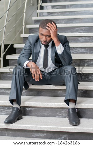 A businessman sits on the stairs with his head in hands. - stock photo