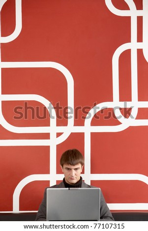 A businessman sitting by the wall concentrated on his laptop - stock photo