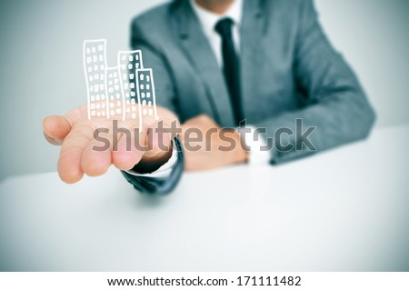 a businessman sitting in a desk showing a pile of drawn buildings in his hand - stock photo
