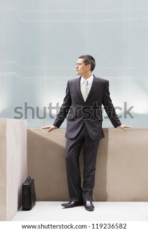A businessman standing against the platform in office