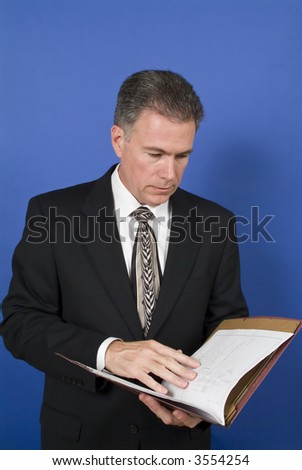 A businessman, standing in front of a blue background, reviewing or conducting a briefing on the contents of the folder. - stock photo