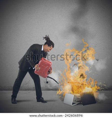 A businessman stressed and pissed burns computers - stock photo