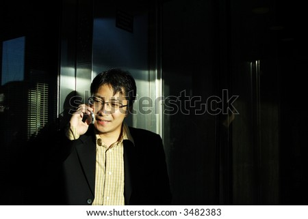 A businessman talking on the phone at the elevator - stock photo