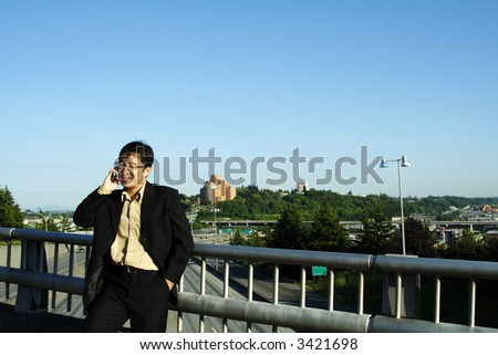 A businessman talking on the phone on a bridge over a highway - stock photo