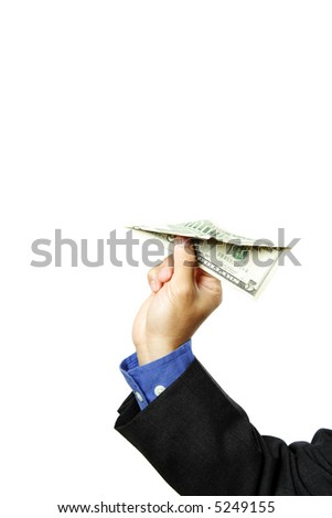 A businessman trying to fly a paper airplane made of dollar bills - stock photo
