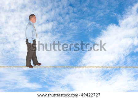 A businessman walks across a tightrope contemplating success, risk, vision and the way forward.