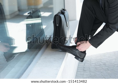 A businessman  wearing a suit is tying his shoes
