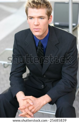 a businessman wearing his business suit sits outside on a seat in thought - stock photo