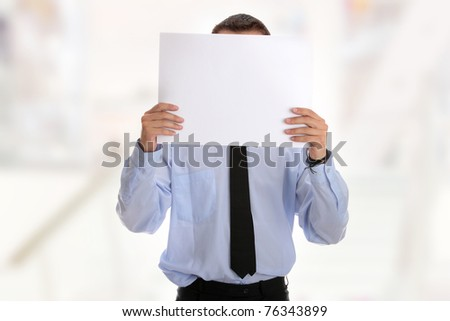 A businessman with a blank paper in his face