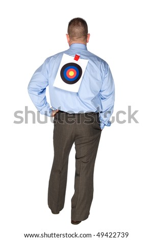 A businessman with a bulls eye taped to his back. - stock photo