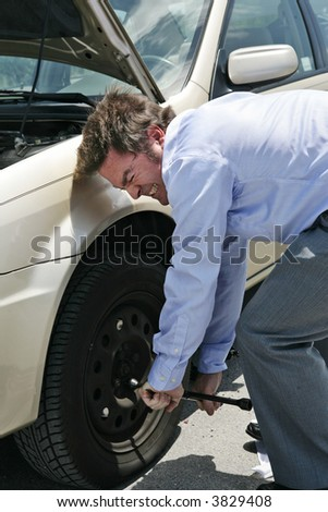 A businessman with a flat tire on the road strains to unscrew the lug nuts. - stock photo