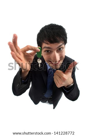 A businessman with a key giving a thumb up. - stock photo