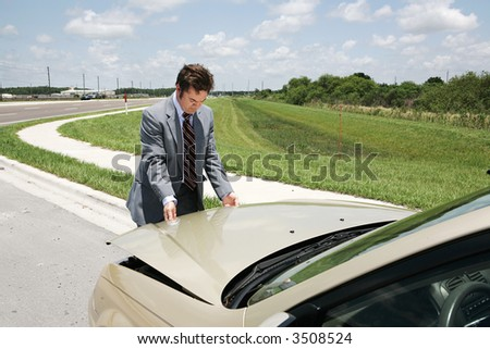 A businessman with car trouble checking under the hood.