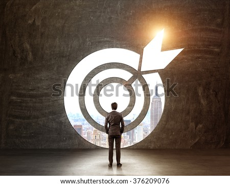 A businessman with hands in pockeys standing in front of a target through which he can see New York. Back view. Black background. Concept of achieving a goal. - stock photo