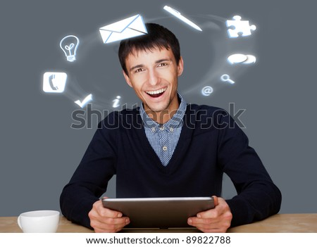 A businessman with icons floating around his head. Portrait of handsome guy working with his tablet pc looking at camera and smiling. Daily deals online. - stock photo