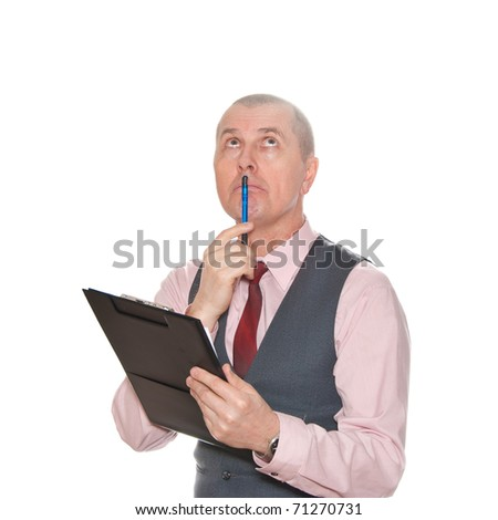 A businessman with pen on his chin looks like he is thinks deeply about something. - stock photo