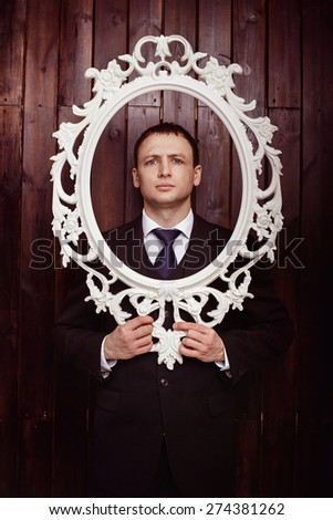 A businessman with serious face is standing at a wooden wall background and holding vintage frame at his face. - stock photo