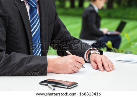 A businessman working by the desk on the grass - stock photo