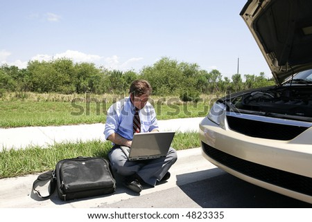 A businessman working in the sun by the side of his broken down car.