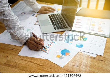 a businessman working plan the business and analysis many chart graph vintage tone sunlight