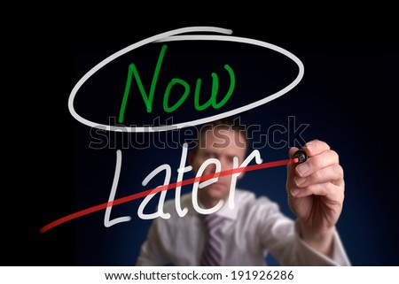 A businessman writing a, Choosing Now instead of Later, concept. - stock photo