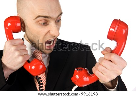 A  businessman yells loudly into the two handsets that he is holding.