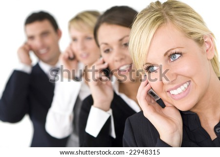 A businesswoman and her three colleagues out of focus behind her all talking on cell phones