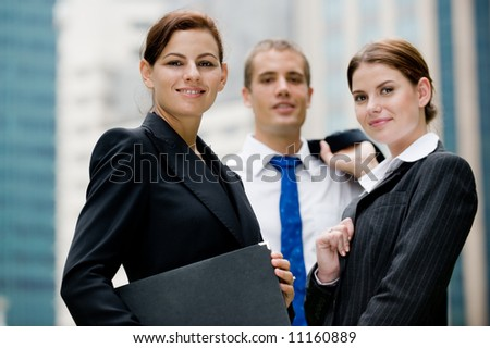A businesswoman and two colleagues outside (shallow depth of field used) - stock photo