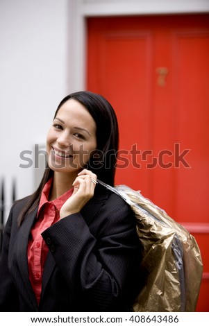 A businesswoman carrying her dry cleaning - stock photo