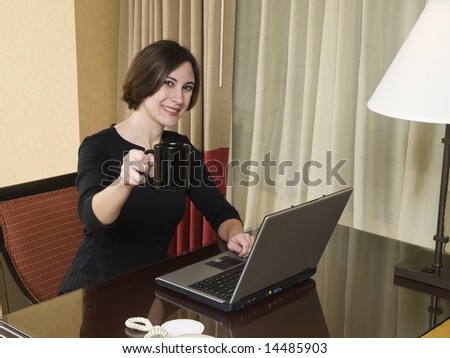 A businesswoman cheerfully reviews good results on her laptop computer in a hotel room during a business trip. - stock photo