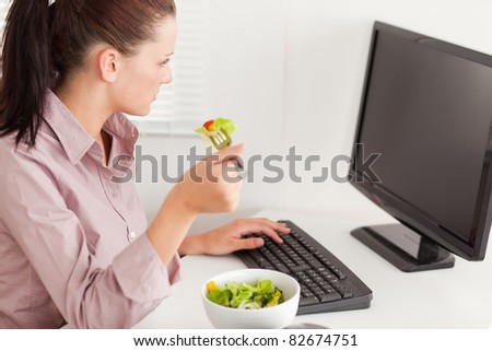 A businesswoman eats salad in her office whilst typing