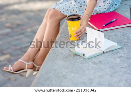 A businesswoman holding a coffee cup sitting on the fountain  - stock photo