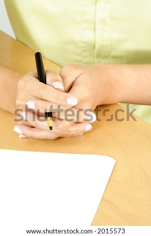 A businesswoman holding a pen ready to write on a piece of blank paper