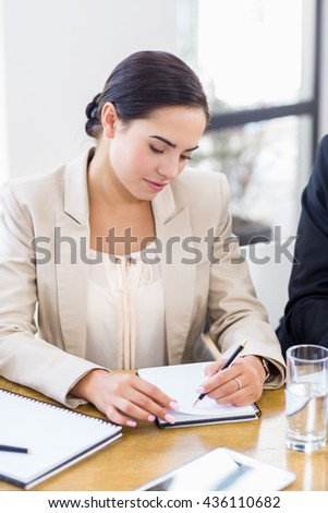 A businesswoman is concentrating and looking at her notes on office