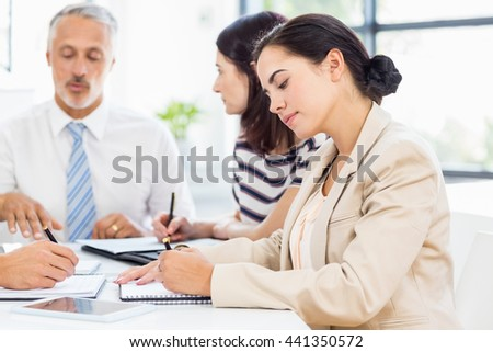 A businesswoman is taking some notes at work - stock photo