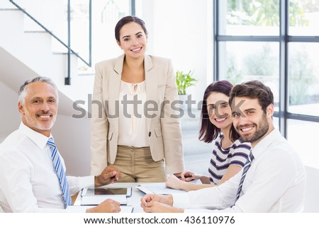A businesswoman is talking to her colleagues who are listening to her at work - stock photo