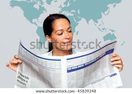 A businesswoman reading a financial newspaper with a map of the world on the wall behind her. - stock photo