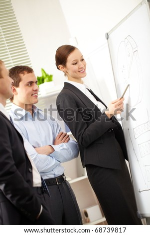 A businesswoman showing a scheme on a whiteboard to her colleagues - stock photo
