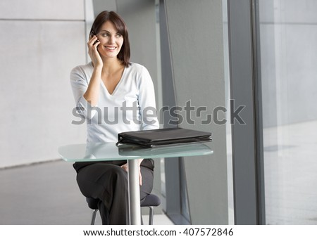 A businesswoman sitting at a glass table, talking on a mobile phone - stock photo