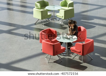 A businesswoman sitting at a table typing on a laptop - stock photo