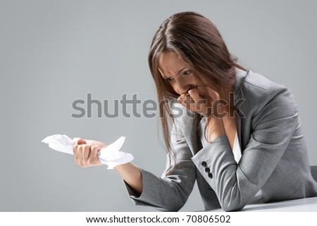 A businesswoman sitting at table and crumpling paper