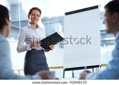 A businesswoman standing by whiteboard and looking at her partners - stock photo