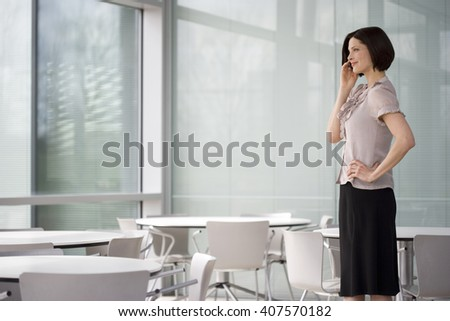 A businesswoman standing by window using a mobile phone - stock photo